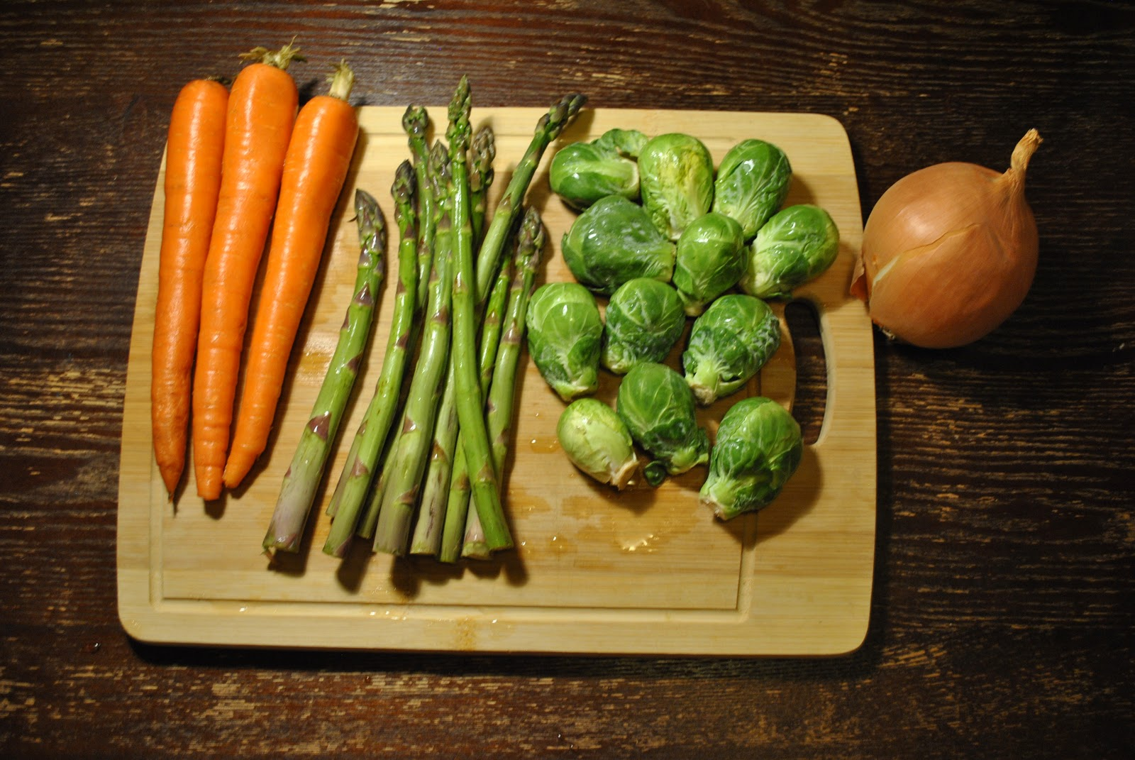 Carrots, asparagus, brussel sprouts, and a yellow onion